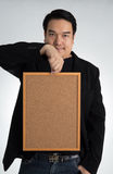 Asian man in black suit holds an empty woodboard Royalty Free Stock Image