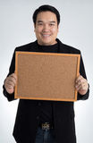 Asian man in black suit holds an empty woodboard Stock Photos