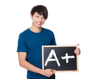 Asian man with the blackboard showing A plus mark Royalty Free Stock Images