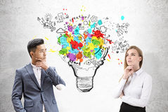 Asian man and blond woman, light bulb Stock Photography