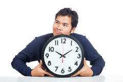 Asian man bored with a clock. Isolated on white background royalty free stock photo