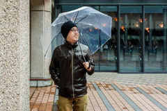 Asian Man in a Brown Jacket With a Clear Umbrella Stock Image