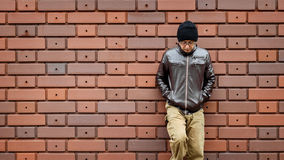 Asian Man in a Brown Jacket Leans Against the Wall Stock Photo