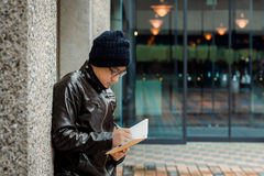 Asian Man in a Brown Jacket with a Small Notebook Stock Photos