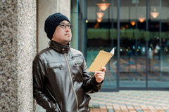 Asian Man in a Brown Jacket with a Small Notebook Stock Photography
