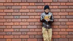 Asian Man in a Brown Jacket with a Small Notebook Royalty Free Stock Photos