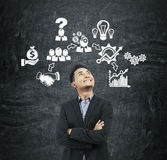 Asian man and business icons on blackboard Royalty Free Stock Image