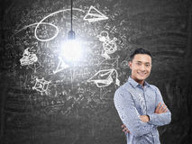 Asian man and business idea. Portrait of a smiling Asian businessman wearing a blue shirt and standing with crosed arms near a blackboard with a business idea Royalty Free Stock Image