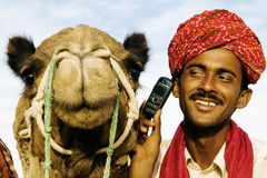 Asian Man and Camel in the Desert with Communications Royalty Free Stock Images