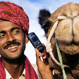 Asian Man and Camel in the Desert with Communications Concept Royalty Free Stock Photo