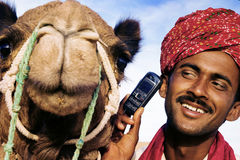 Asian Man and Camel in the Desert with Communications Concept Royalty Free Stock Images