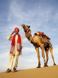 Asian Man and Camel in the Desert with Communications Stock Photos