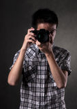 Asian Man with Camera. Asian man taking pictures with a slr camera Royalty Free Stock Images