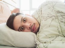 Man try to sleep in the morning with sleepless black eyes. Asian man can not sleep in the morning light with sleepless black eyes Royalty Free Stock Image
