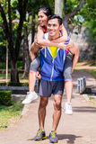 Asian man carrying his girlfriend piggyback for sport Stock Images
