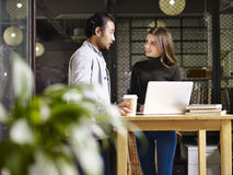 Asian man and caucasian woman discussing business in office Stock Photography