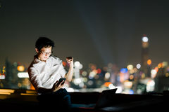 Asian man celebrate with smartphone and laptop computer, success pose. Business, job, or communication gadget technology concept Stock Images