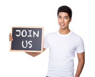 Asian man with chalkboard showing a phrase of join us Stock Photo