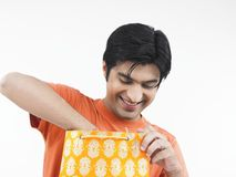 Asian man checking his shopping bag. Asian male of indian origin looking through his shopping bag Stock Images