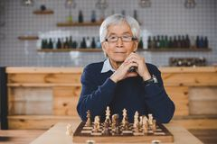 Asian man with chess board. Senior thoughtful asian man with chess board sitting in bar Stock Images