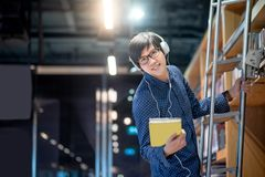 Asian man choosing book on ladder in library. Young Asian man student choosing book from bookshelf using ladder in public library, Male researcher with Royalty Free Stock Photography