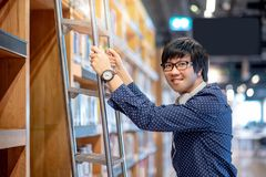 Asian man choosing book on ladder in library. Young Asian man student choosing book from bookshelf using ladder in public library, Male researcher with Royalty Free Stock Image