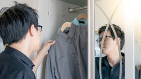 Asian man choosing shirt in closet. Young Asian man choosing casual style shirt in closet for dressing up in the bedroom. Home living lifestyle concept stock image