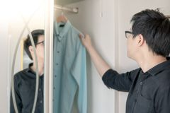 Asian man choosing shirt in closet. Young Asian man choosing casual style shirt in closet for dressing up in bedroom. Home living lifestyle concept royalty free stock photo