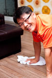 Asian man cleaning floor. Smiling Asian man kneeling and cleaning the floor royalty free stock photo