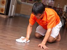 Asian man cleaning floor. Smiling Asian man kneeling and cleaning the floor royalty free stock photos