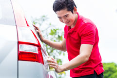Asian man cleaning and washing car with sponge Stock Photos