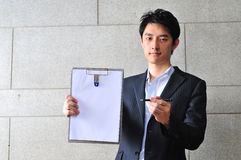 Asian Man with Clipboard asking for signature Royalty Free Stock Photo