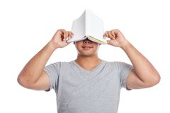 Asian man close his face with a book and smile. Isolated on white background stock photos