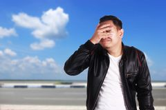 Asian Man Closing His Eyes. Portrait of young funny Asian man wearing black leather jacket closing his eyess as if he is scared to see something bad, ignoring royalty free stock photo