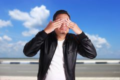 Asian Man Closing His Eyes. Portrait of young funny Asian man wearing black leather jacket closing his eyess as if he is scared to see something bad, ignoring royalty free stock photos
