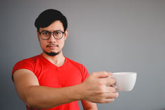 Asian man and coffee cup. Royalty Free Stock Image