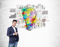 Asian man with coffee and light bulb with charts Stock Image