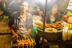 Asian man cooking meat in the street market in Vietnam Royalty Free Stock Image