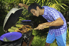 Asian man cooking on an outdoor grill Stock Photos