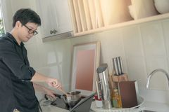 Asian man cooking with pot and ladle in kitchen. Asian man cooking with stainless pot and ladle on electric stove watching cooking instructions on digital tablet royalty free stock images