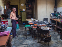 Asian man cooks jerky in home kitchen. A Malaysian man cooks pork jerky in his kitchen in Penang. He smokes a cigarette and has his shirt off Royalty Free Stock Photography
