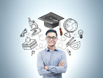 Asian man with crossed arms, education icons Royalty Free Stock Photography