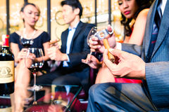 Asian man cutting cigar in restaurant Royalty Free Stock Photo