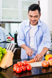 Asian man cutting salad in kitchen Royalty Free Stock Photo