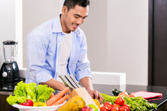 Asian man cutting vegetables and salad Stock Photo