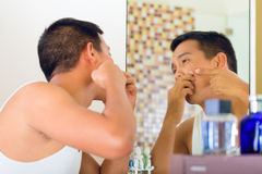 Asian man discovering a pimple. In face royalty free stock photos