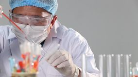 Asian Man Doctor with mask, rubber, helmet and eyes wear,  checking drop liquid chemical into glass tube plate. stock footage