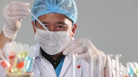 Asian Man Doctor with mask, rubber, helmet and eyeswear,  checking drop liquid chemical into glass tube plate. Color Red, blue, ye stock footage