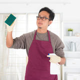 Asian man doing house chores Royalty Free Stock Images