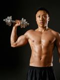 Asian man doing single shoulder press. Photo of an Asian male exercising with dumbbells and doing a single shoulder press over dark background stock photo